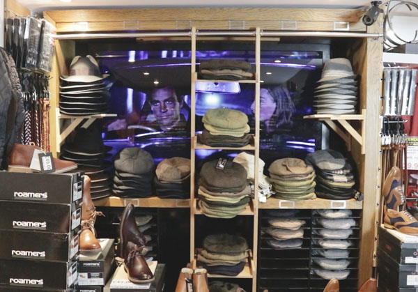 James Bond showing on the screen in the shop behond the hat shelves